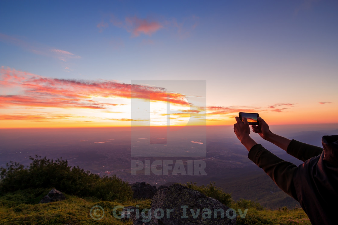 """""""hand shooting the sunrise over the city in Bulgaria"""" stock image"""