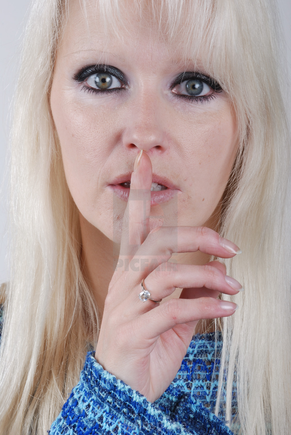 """""""Young blond woman finger over her mouth"""" stock image"""