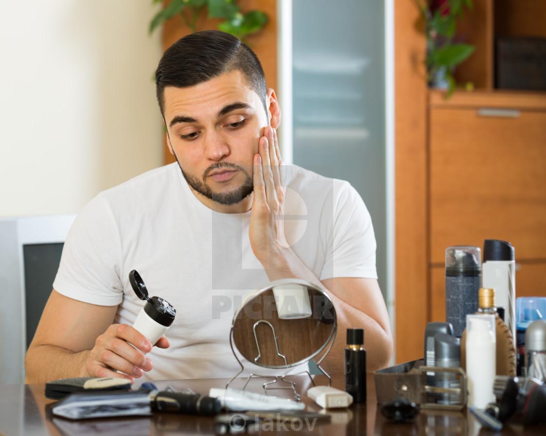 """man applying facial cream at home"" stock image"