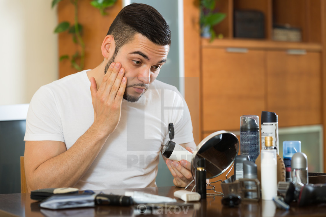 """Man applying cream on face skin"" stock image"
