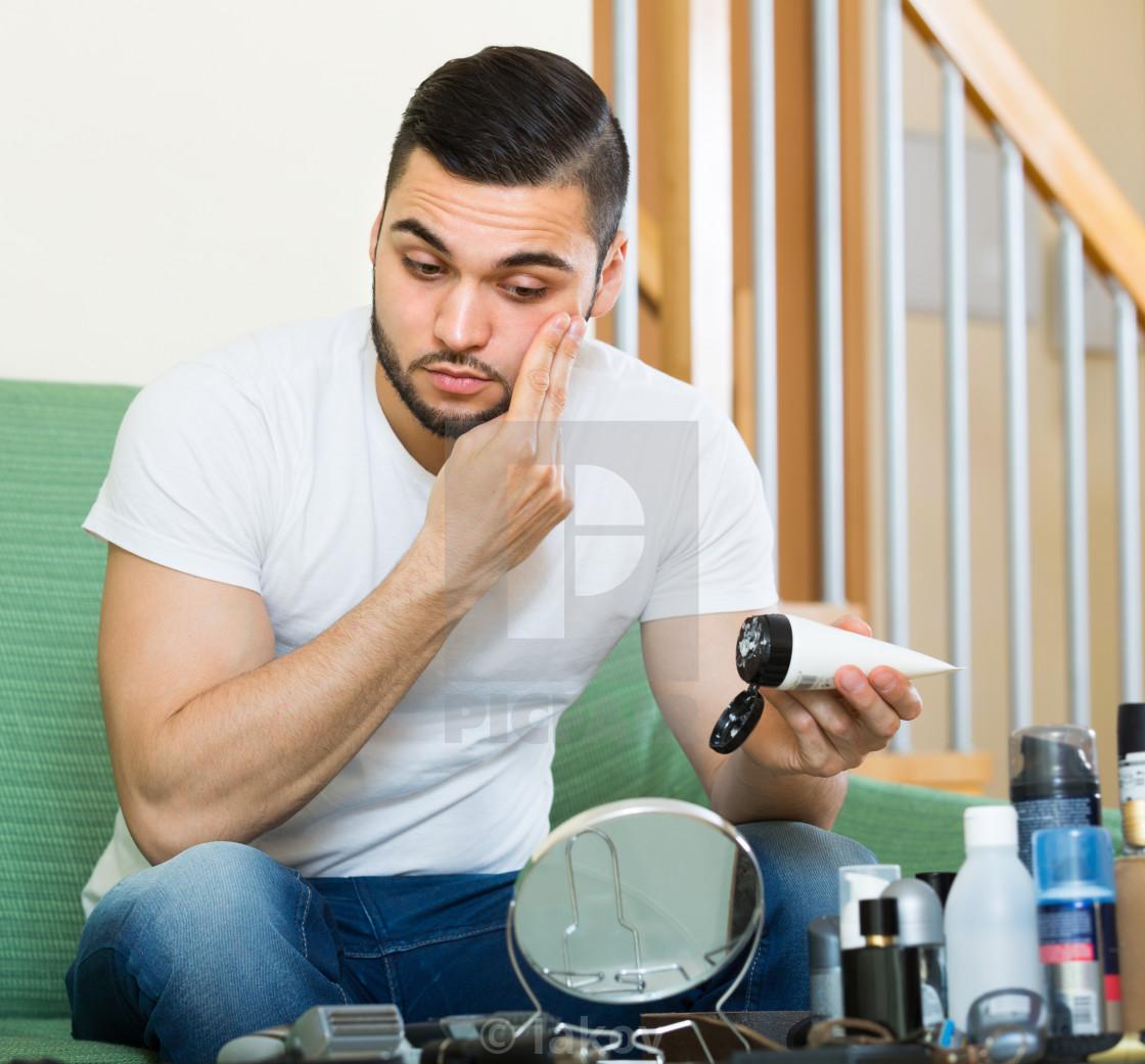 """Man applying cream on face skin ."" stock image"
