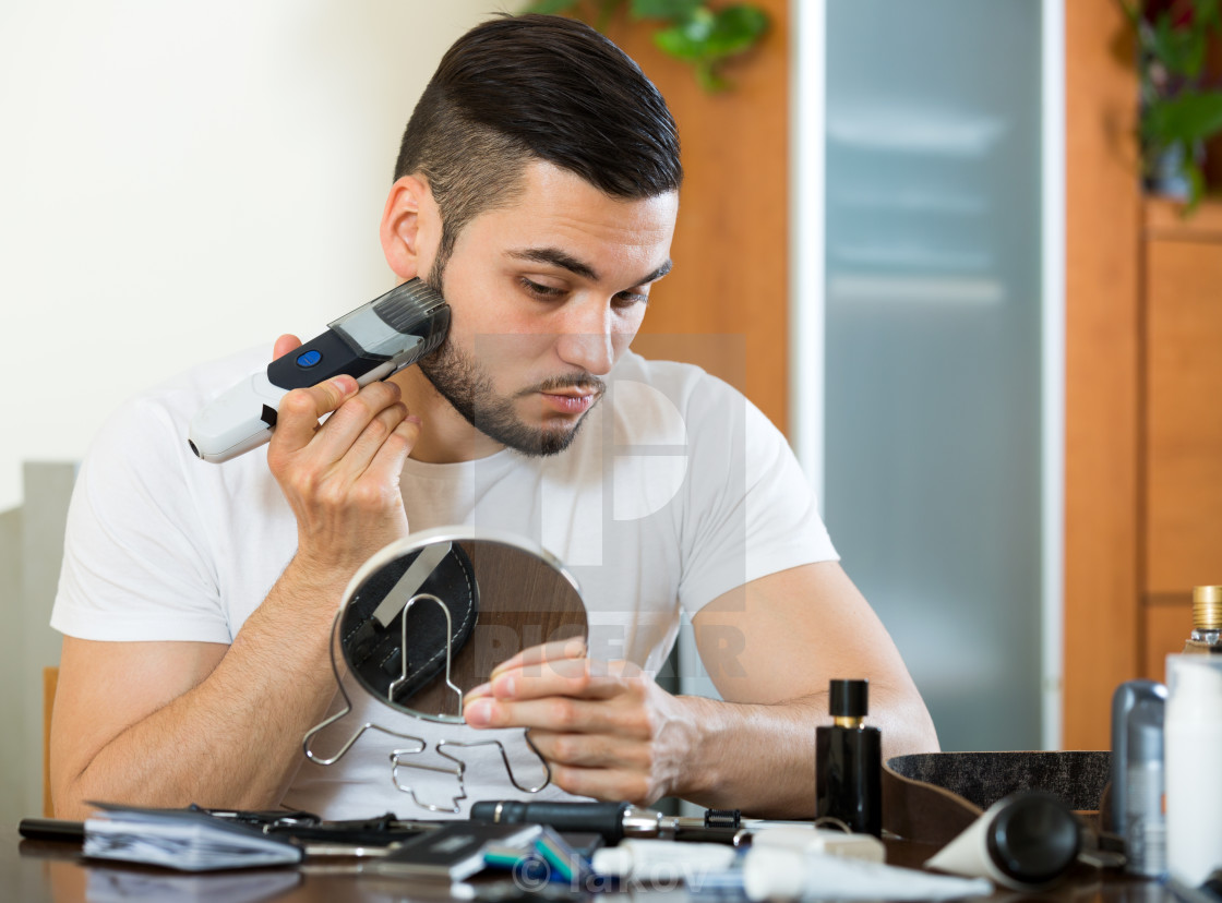 """""""Shaving face with electric razor"""" stock image"""