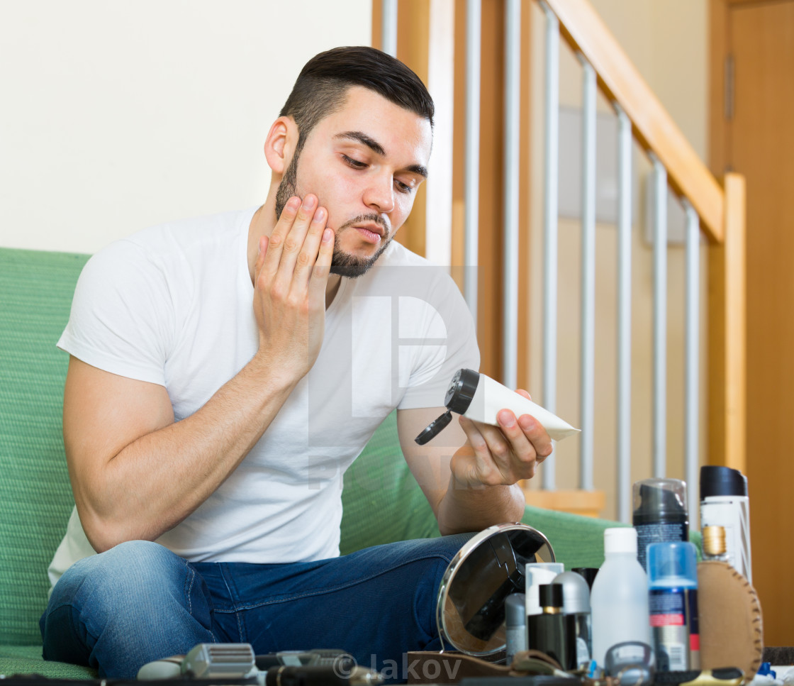 """""""Handsome man applying facial cream at home"""" stock image"""