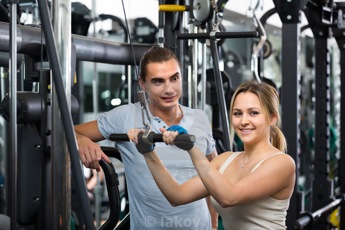 """Young adults working out in fitness club"" stock image"