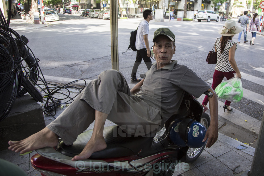 """Man resting on a scooter in Vietnam."" stock image"
