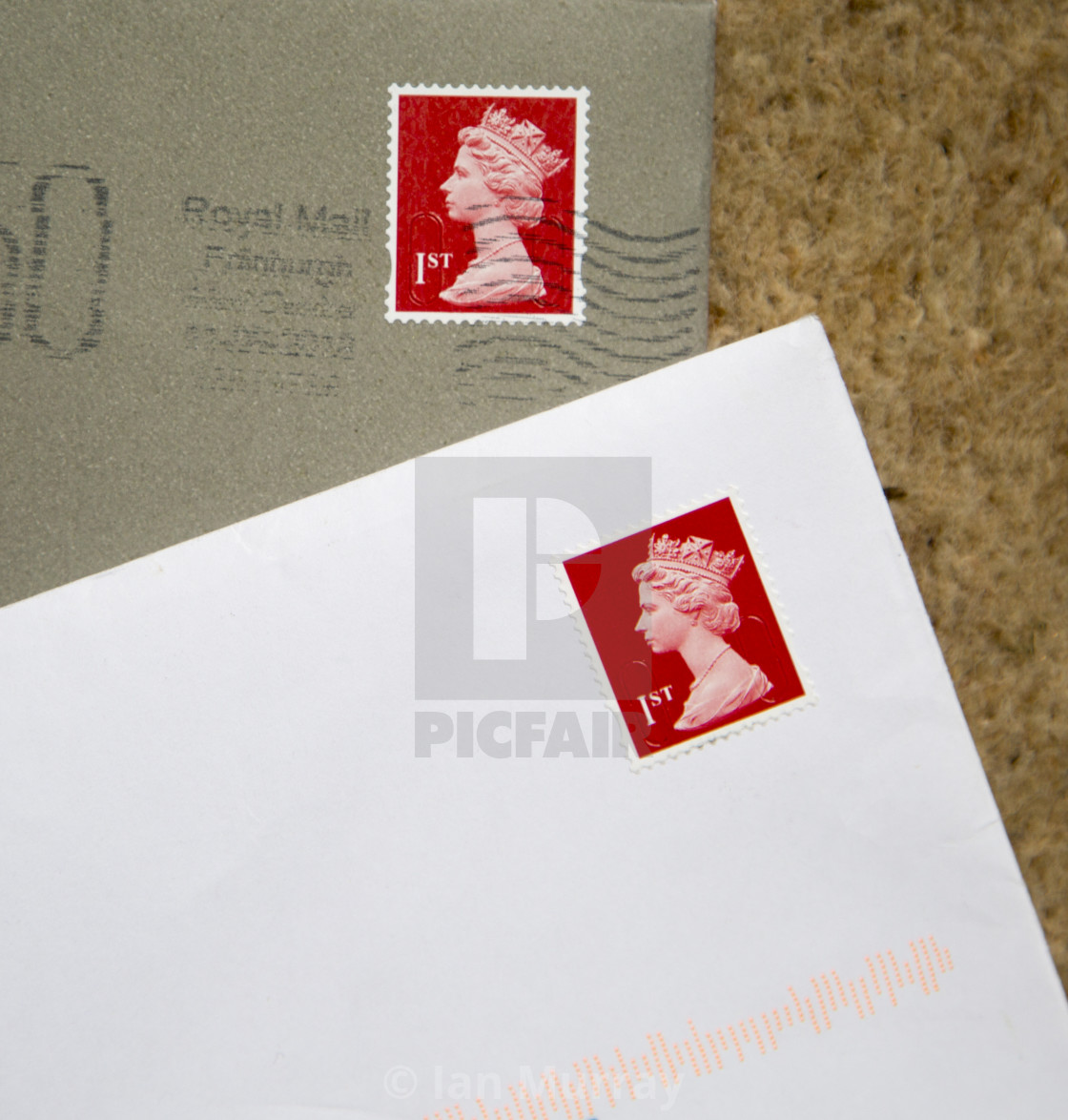 """Looking down at letters in envelopes with red First class postage stamps,."