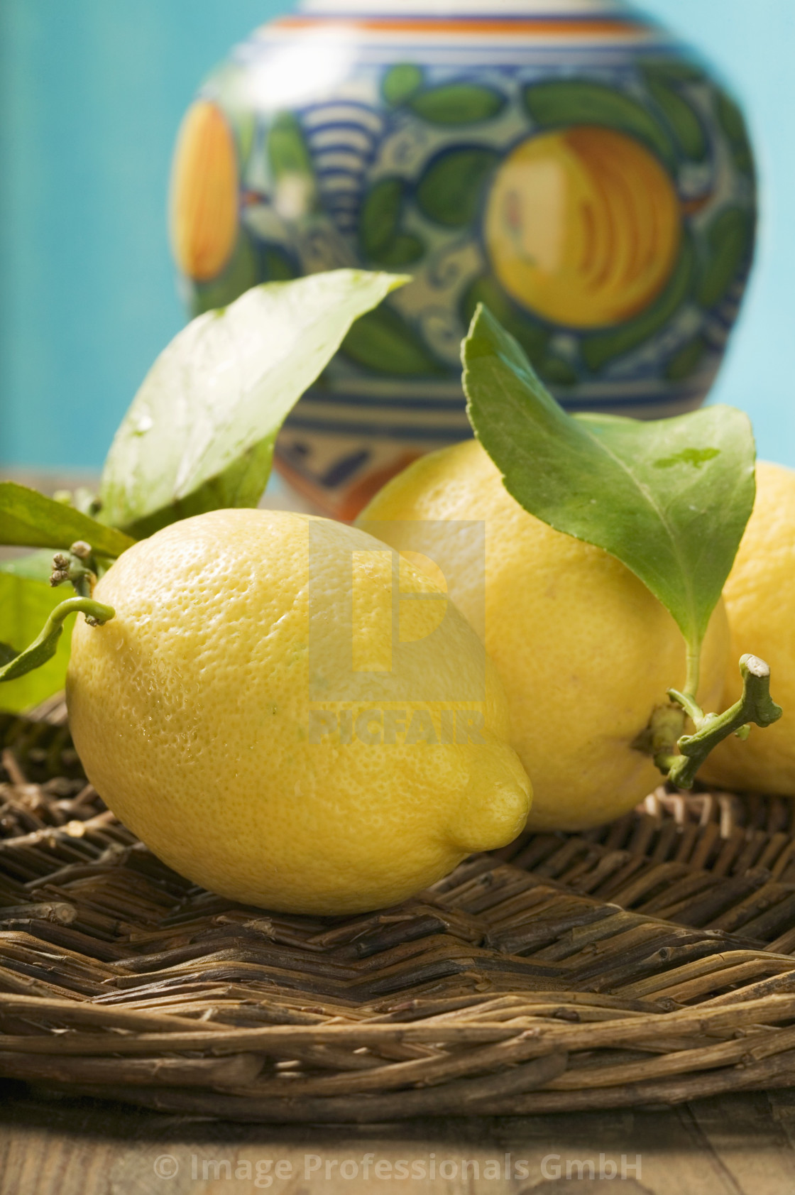 """Fresh lemons with leaves on wicker tray"" stock image"