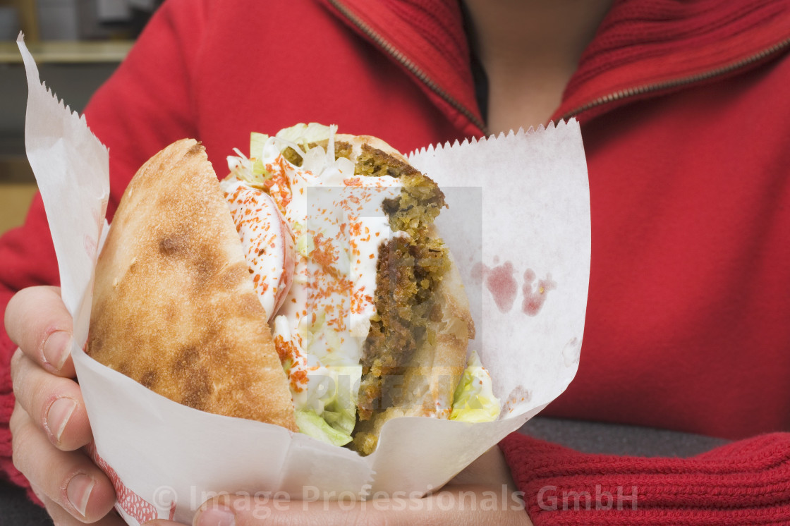 """""""Person holding pita bread filled with falafel in snack bar"""" stock image"""
