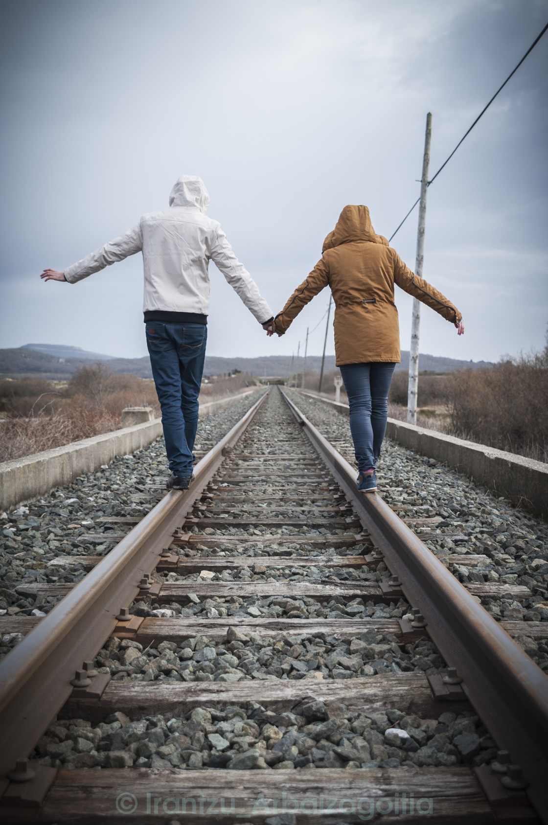 """Young couple walking on a railway. Rural setting"" stock image"