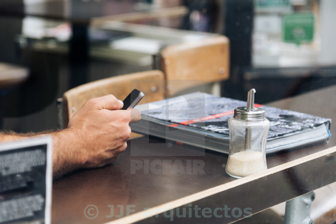 """Man hand holding a phone at the cafe"" stock image"