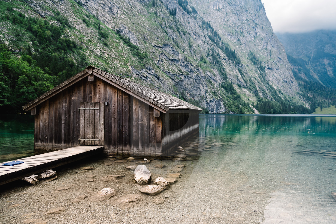 """Wooden cottage in beautiful lake in the Alps with misty mood"" stock image"