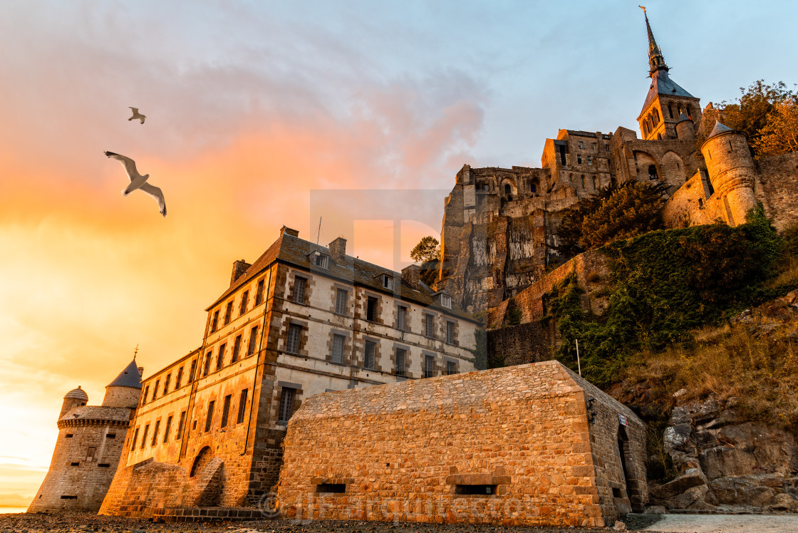 """Seagulls flying over dramatic sunset in Mont Saint-Michel"" stock image"