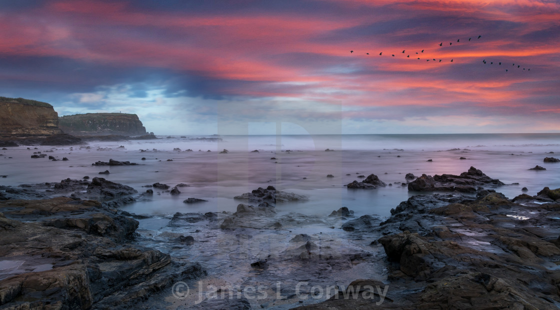 """Sunrise over Rocky Coastline"" stock image"