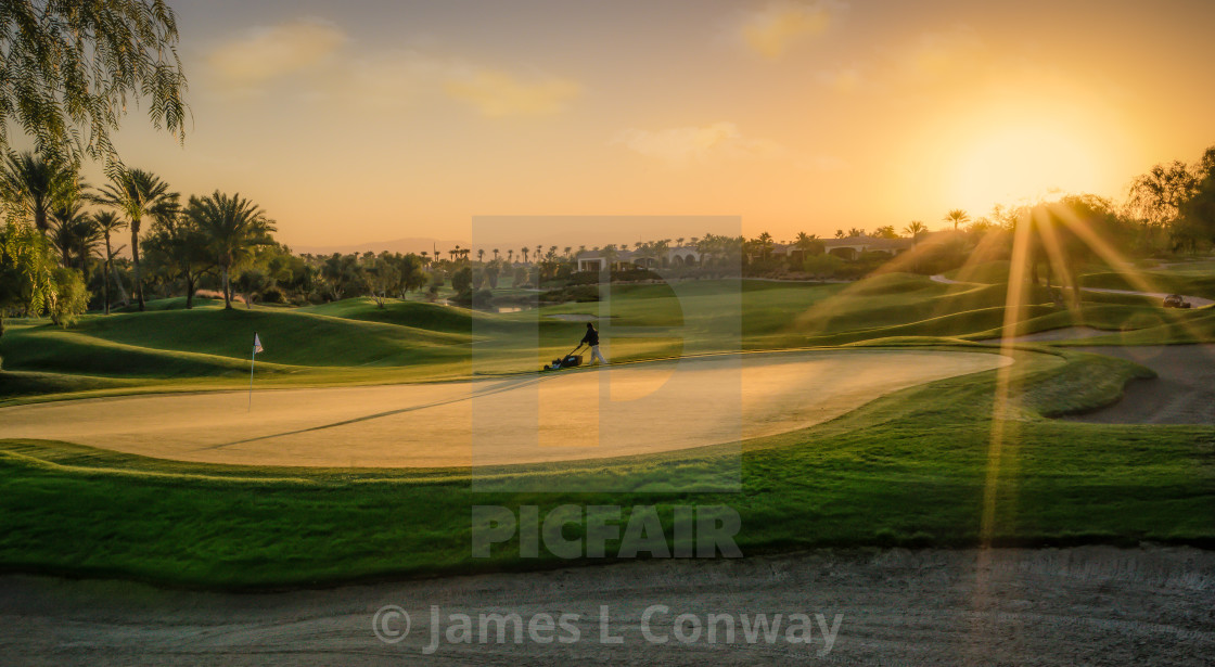 """Mowing Golf Green at Dawn"" stock image"