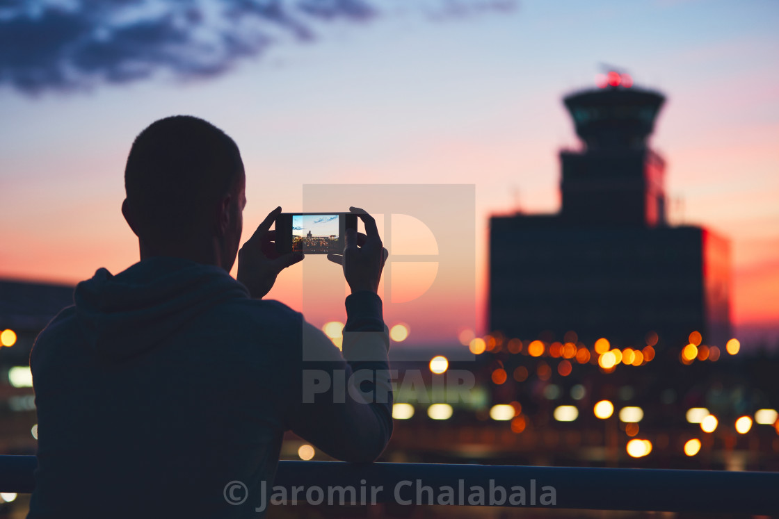 """""""Silhouette of the traveler with mobile phone at the airport. Air Traffic Control Tower at the amazing sunset. Prague, Czech Republic."""" stock image"""