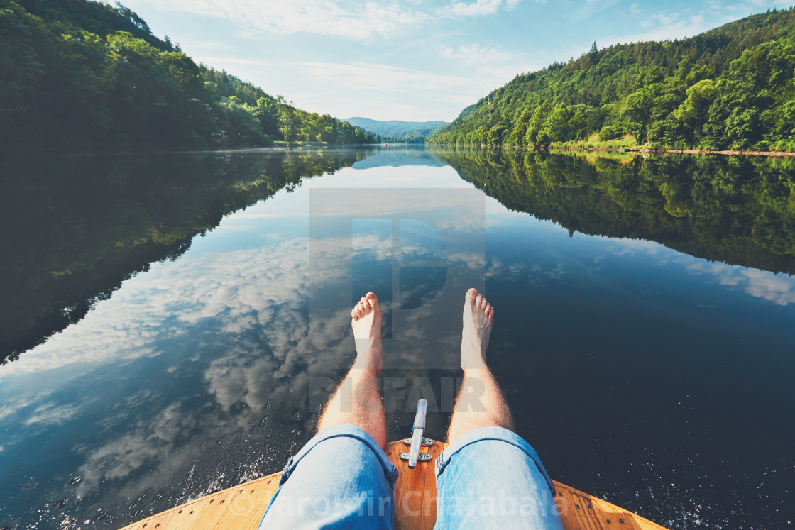 """Summer relaxation on the river. The legs of a man sitting on the bow of the boat. Vltava river near Prague, Czech Republic"" stock image"