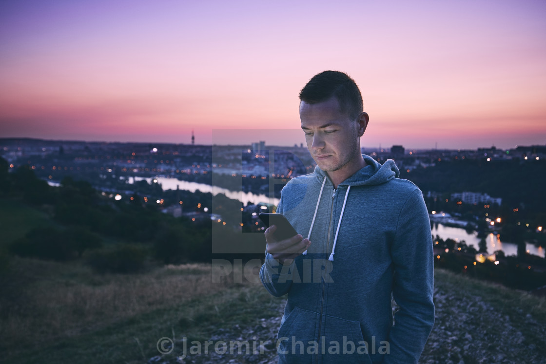 """Man using phone at sunrise"" stock image"