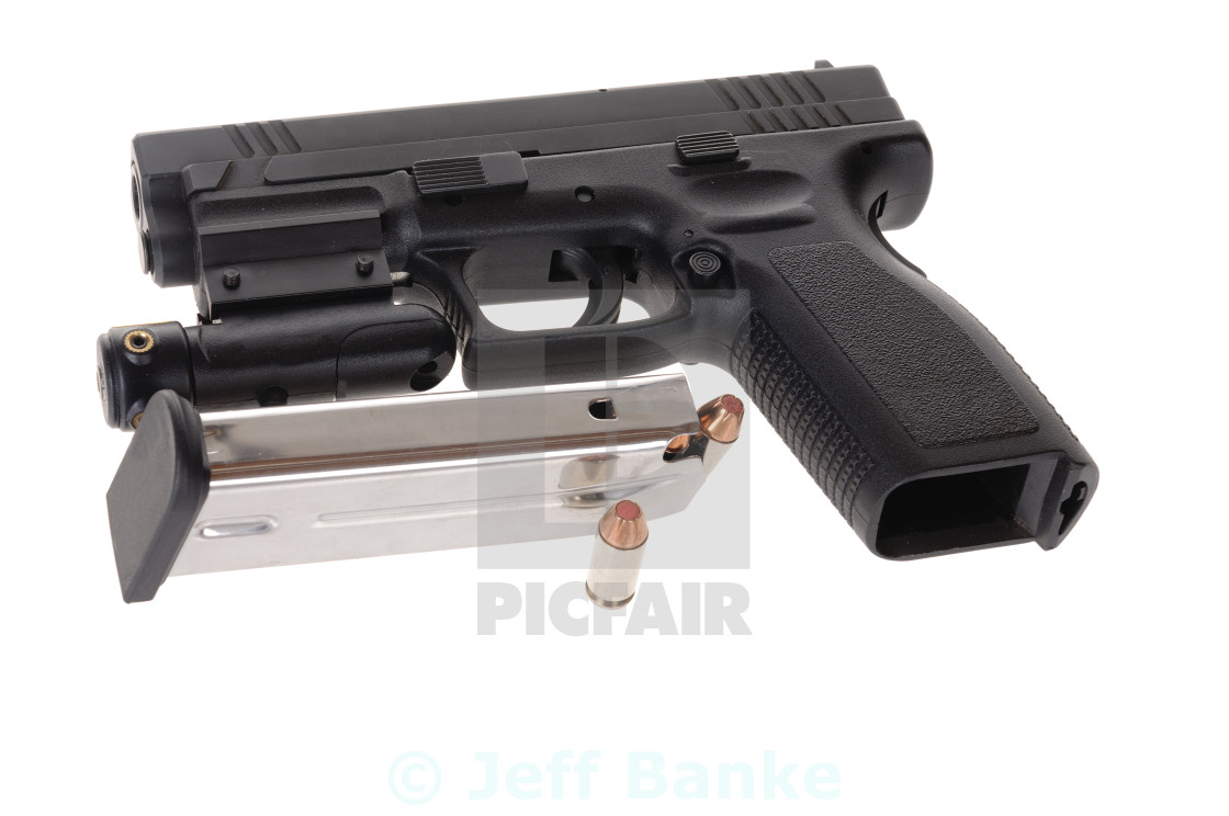 """Semi-auto handgun equipped with a laser sight, and a magazine isolated on white"" stock image"