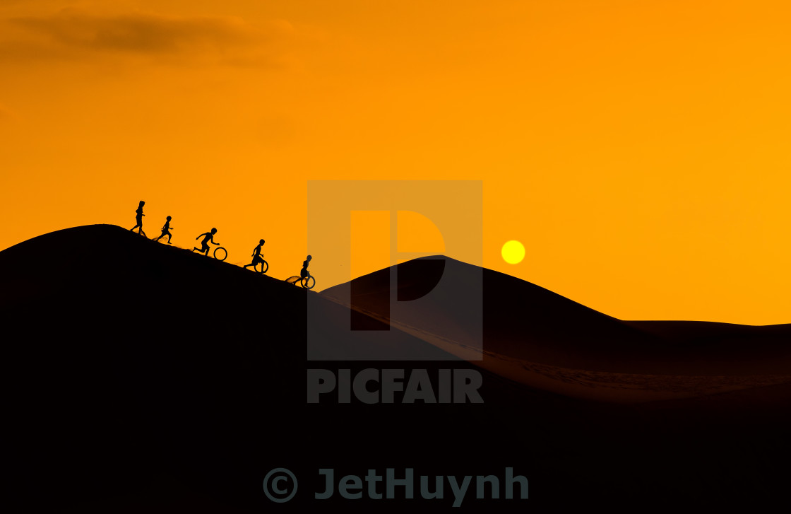 """Silhouette of children playing on sand hill - Vietnam landscape"" stock image"