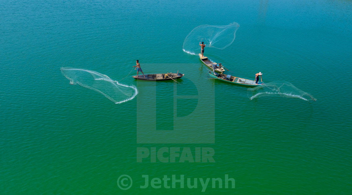 """Throwing fishing net at the lake"" stock image"