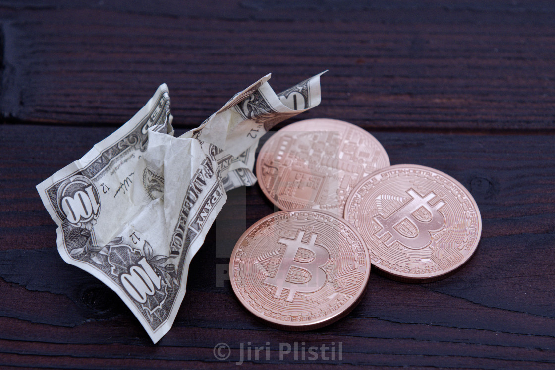 """Dollar banknotes and Bitcoins on a wooden table"" stock image"