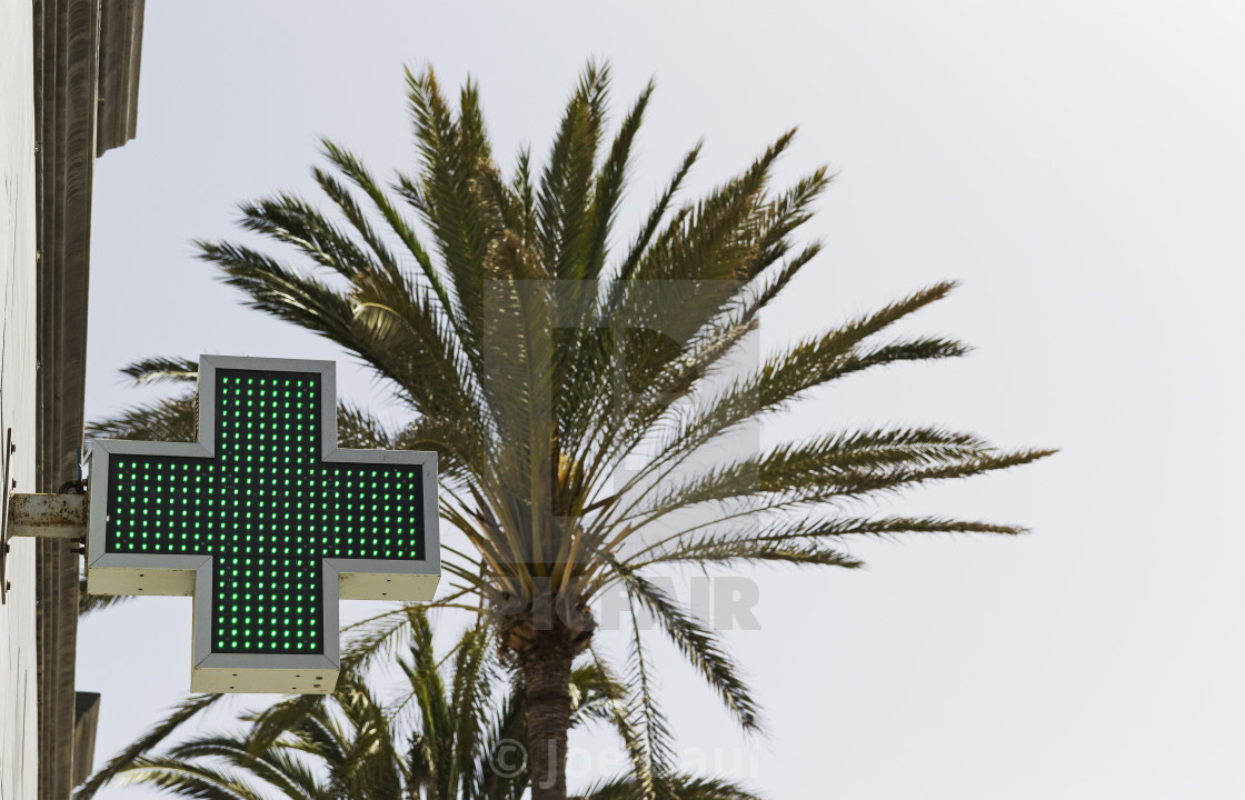 """Green and white pharmacy sign with palm tree background."" stock image"