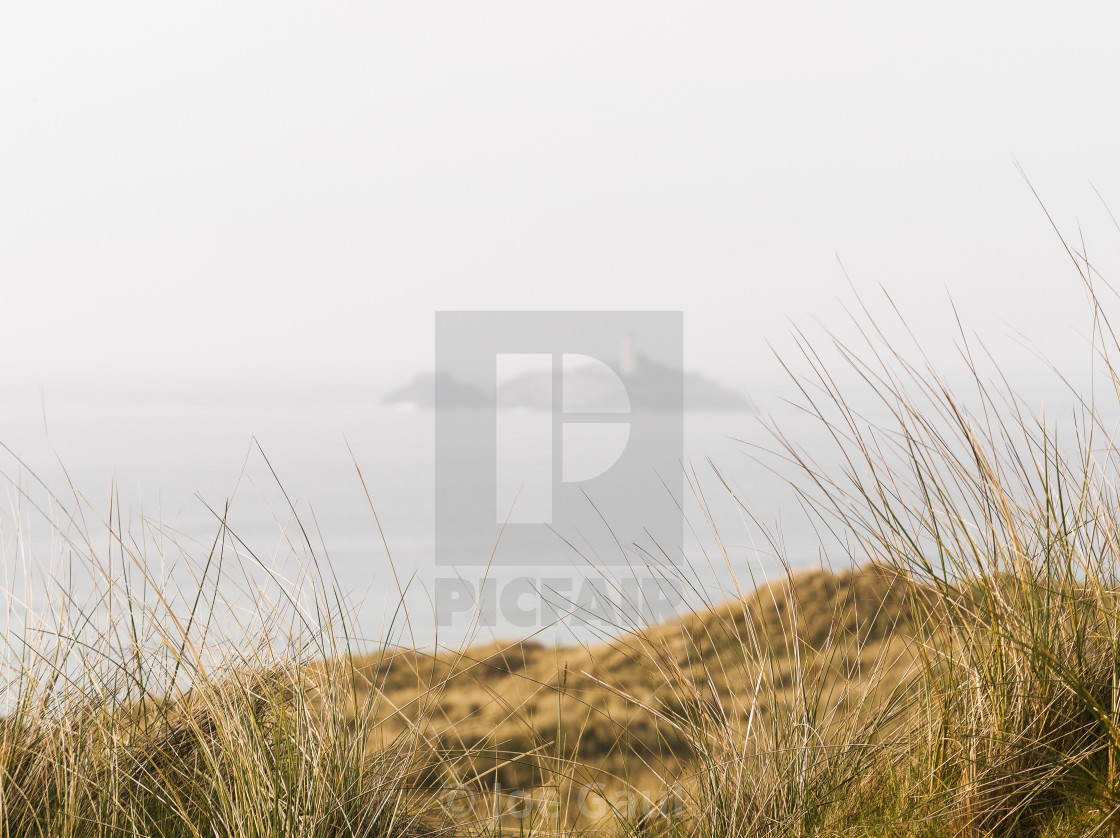 """Grasses at UK coast with defocussed lighthouse in background."" stock image"