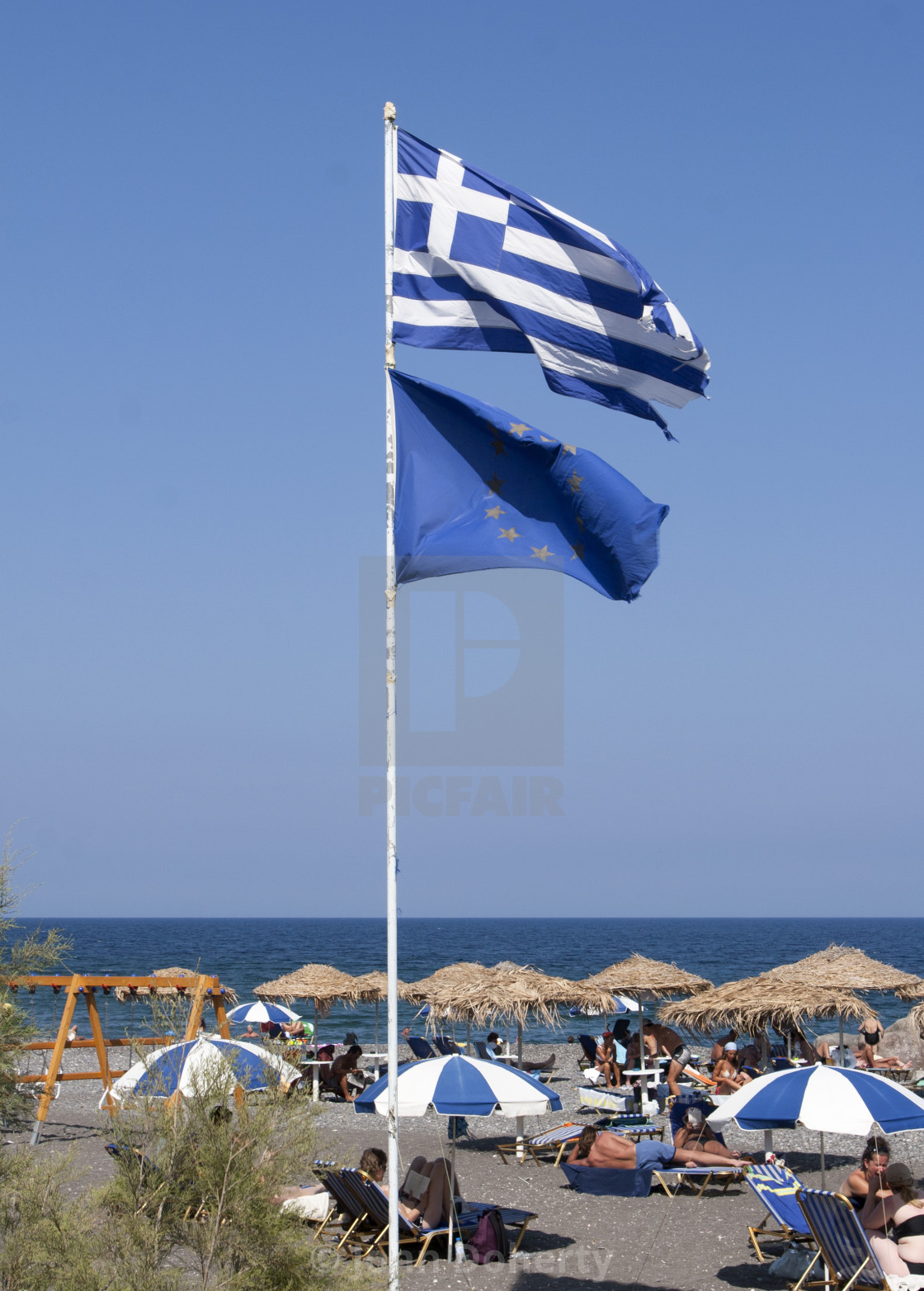 """The Greek and European Union Flags Flying on Perissa Beach"" stock image"