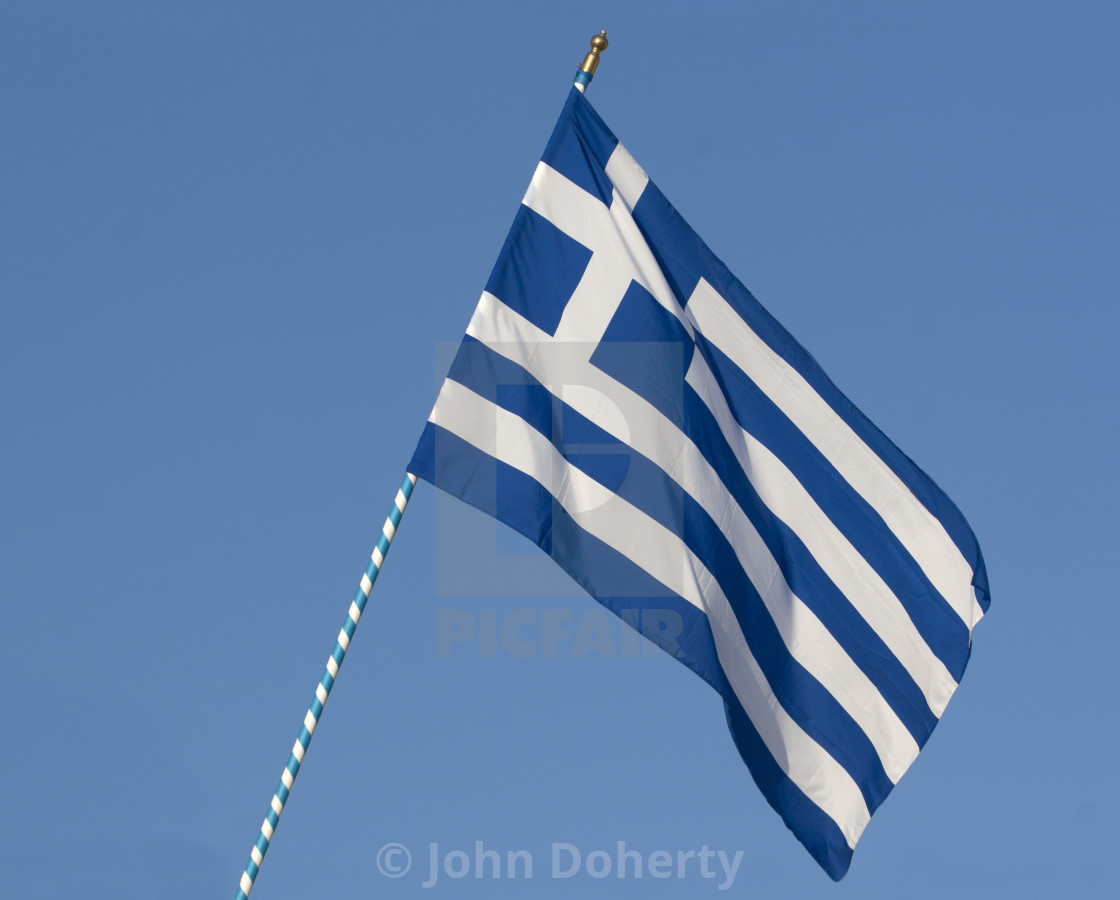 """Greek Flag flying over Santorini"" stock image"