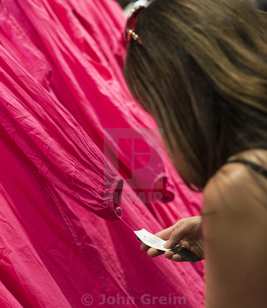"""""""Woman bargain hunting in clothing store"""" stock image"""