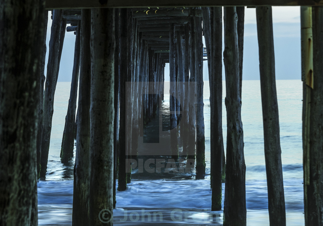 """Ocean waves under a fishing pier"" stock image"