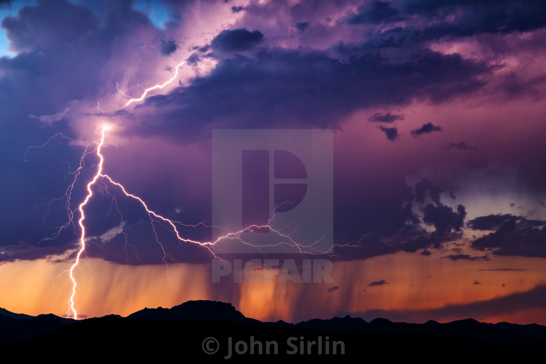 """""""Lightning bolt from a sunset thunderstorm in the Arizona desert."""" stock image"""