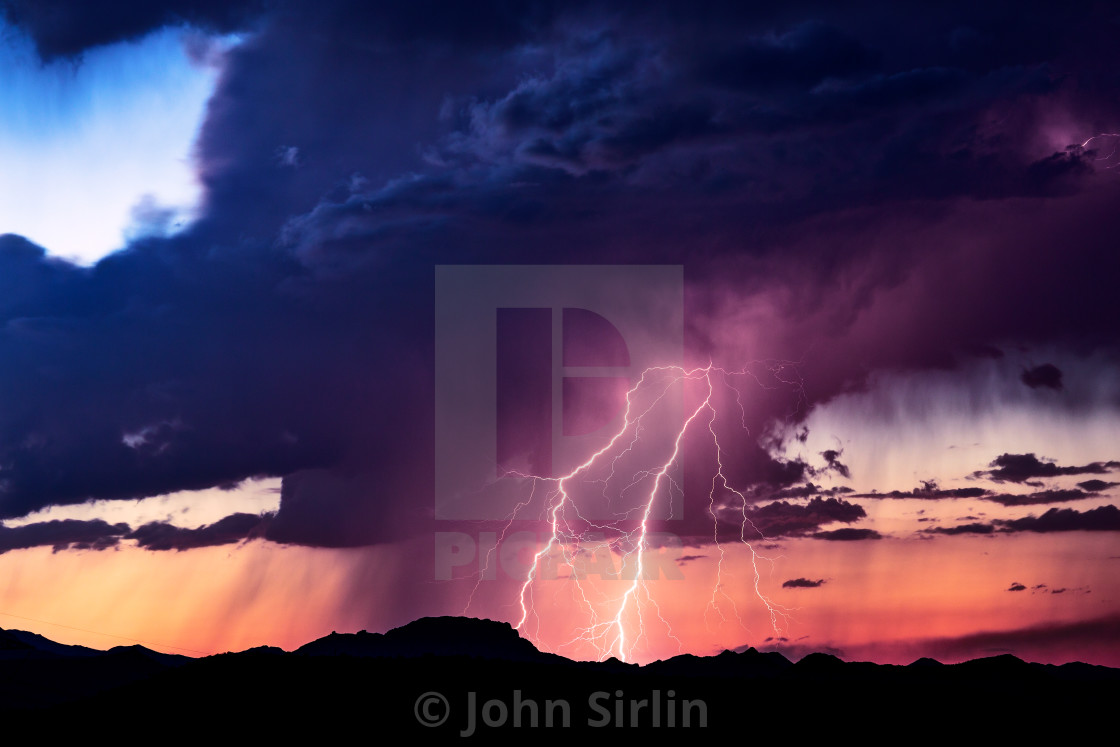 """Lightning bolts strike from a monsoon storm at sunset."" stock image"