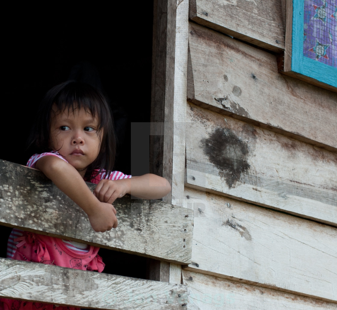 """Young girl looking out of her hut, Mulu, Borneo"" stock image"