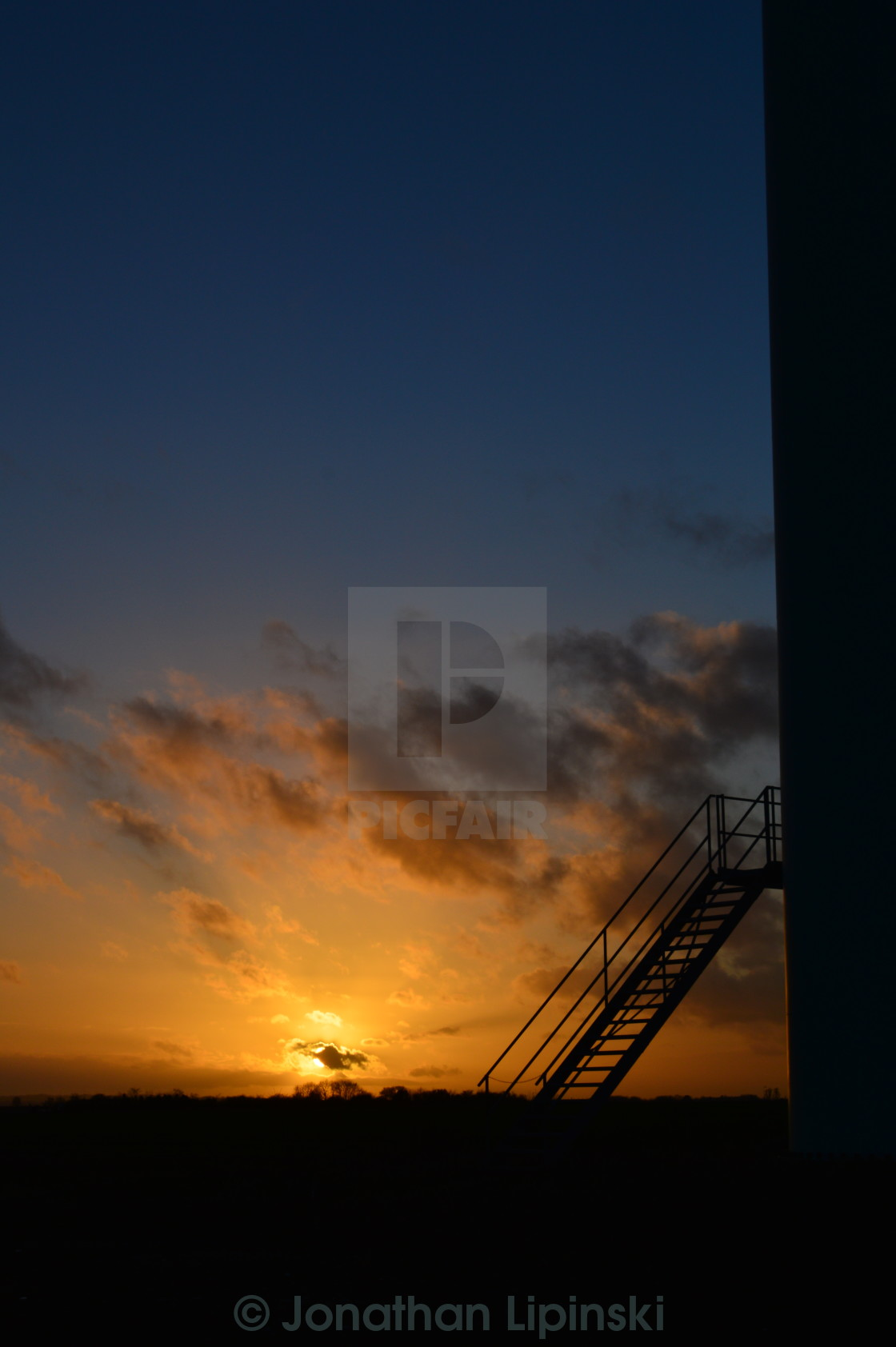 """Sunset on a windfarm with a turbine"" stock image"