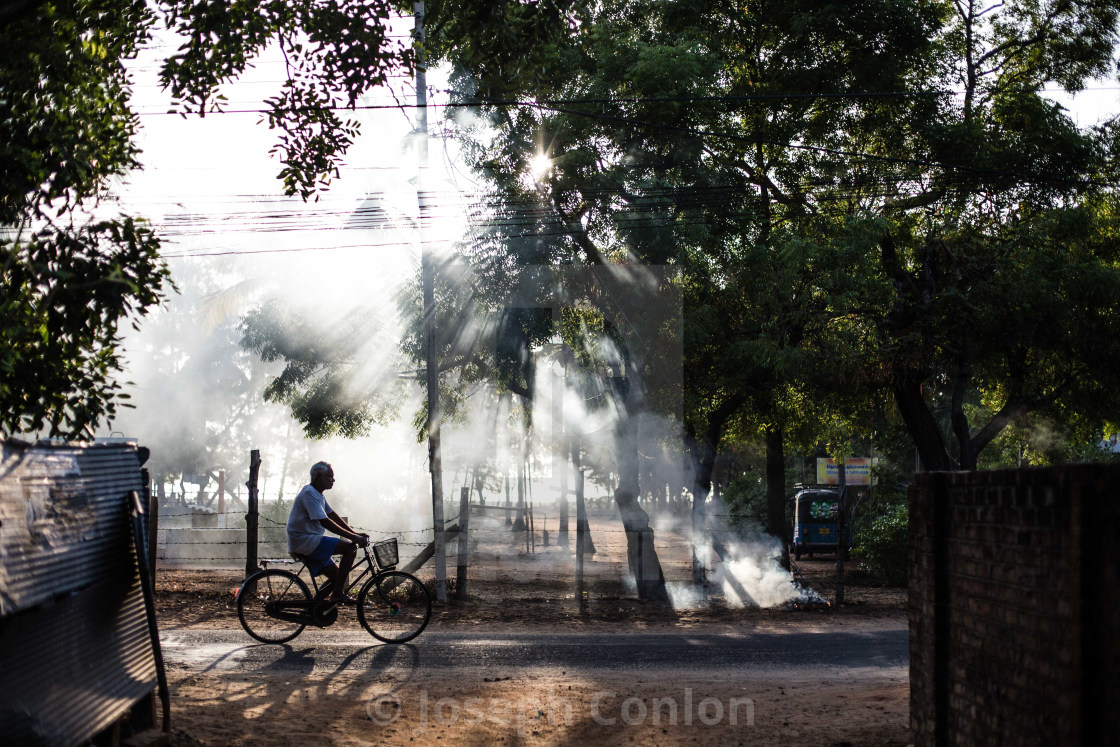 """Cyclist at dawn in Batticaloa, Sri Lanka"" stock image"
