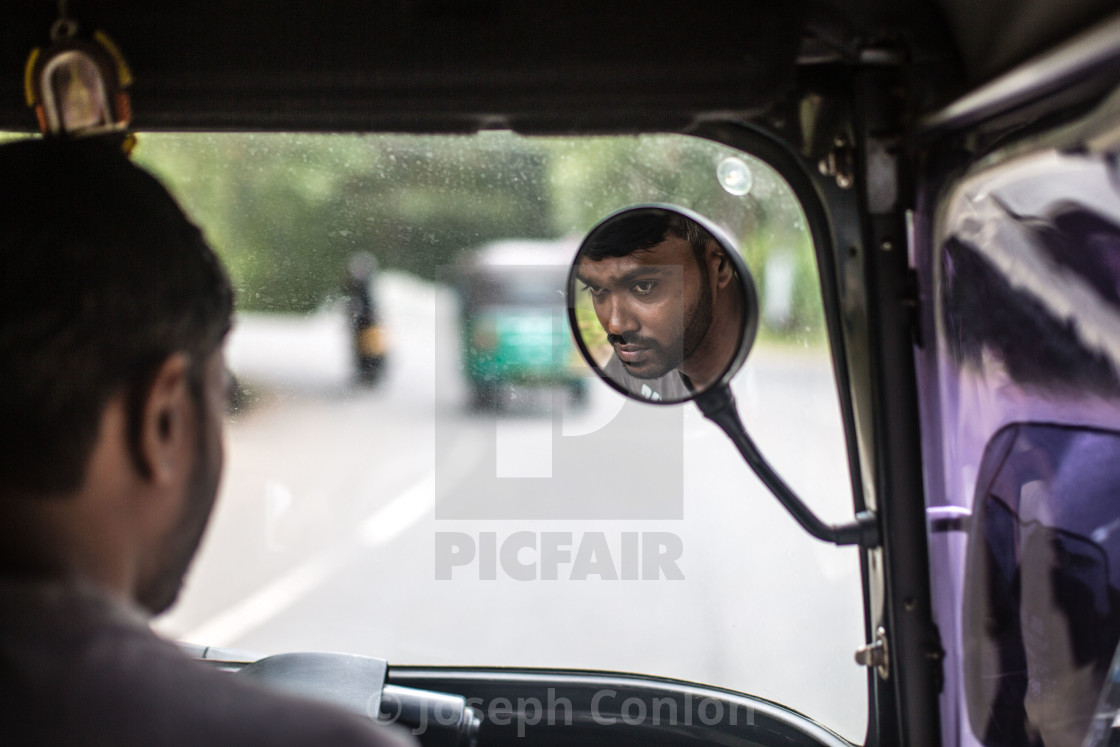 """Reflection of mans face in Tuk Tuk Taxi, Sri Lanka"" stock image"