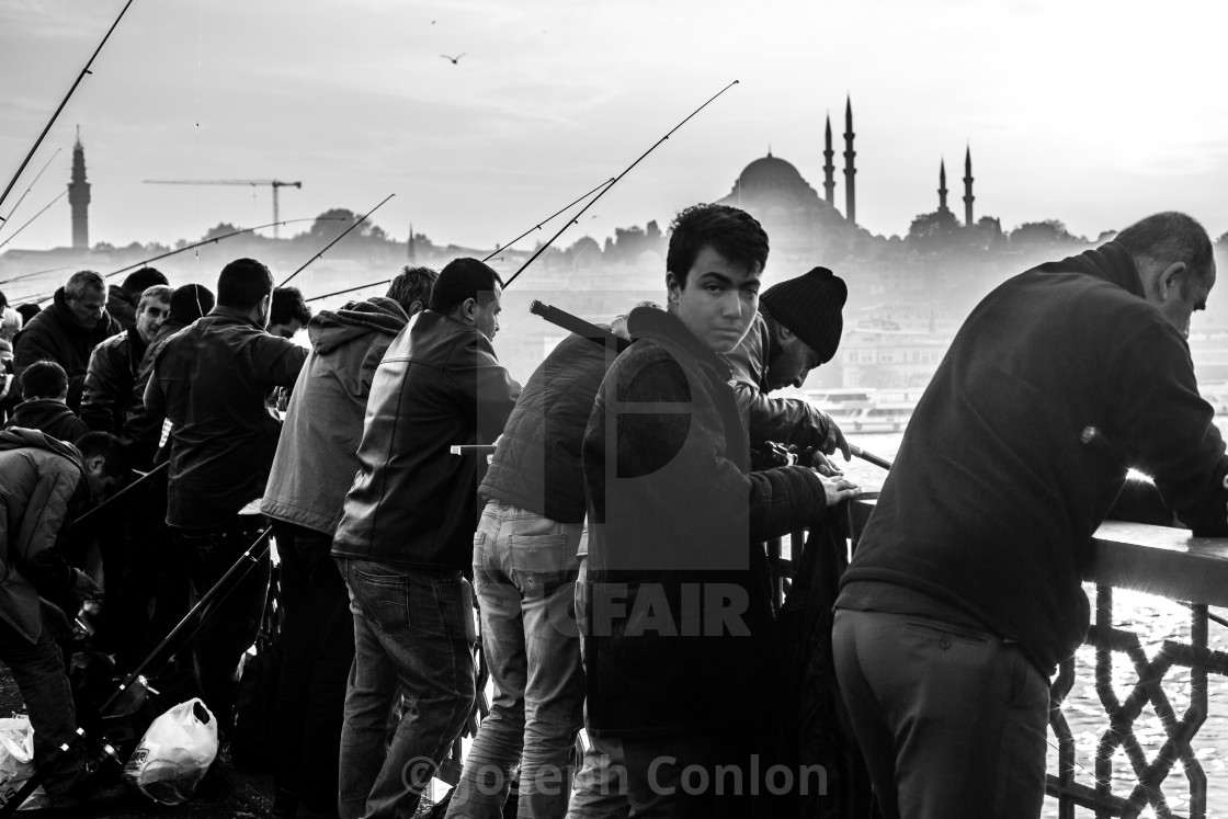 """Boy Fishing on Gattaca Bridge, Istanbul, Turkey"" stock image"