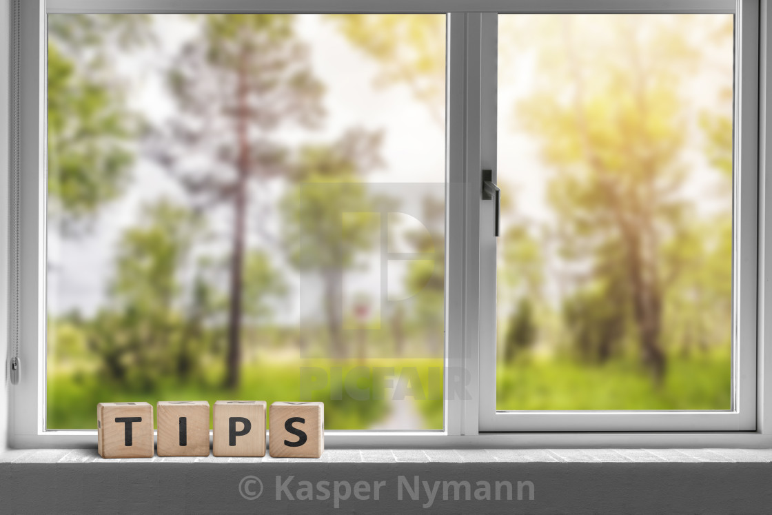 """""""Tips sign in a window with a view to a green garden"""" stock image"""