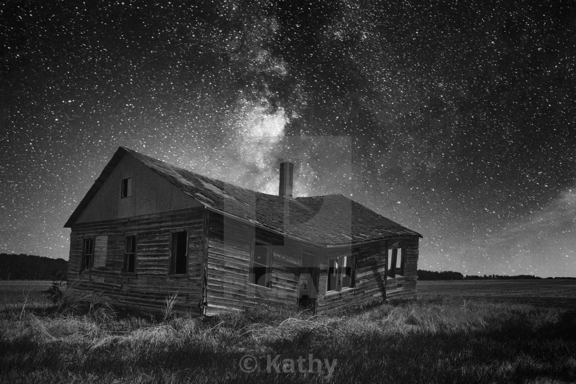 """An old weathered and faded clapboard farmhouse sagging in the middle under a starry night sky in a black and white countryside nighttime landscape"" stock image"
