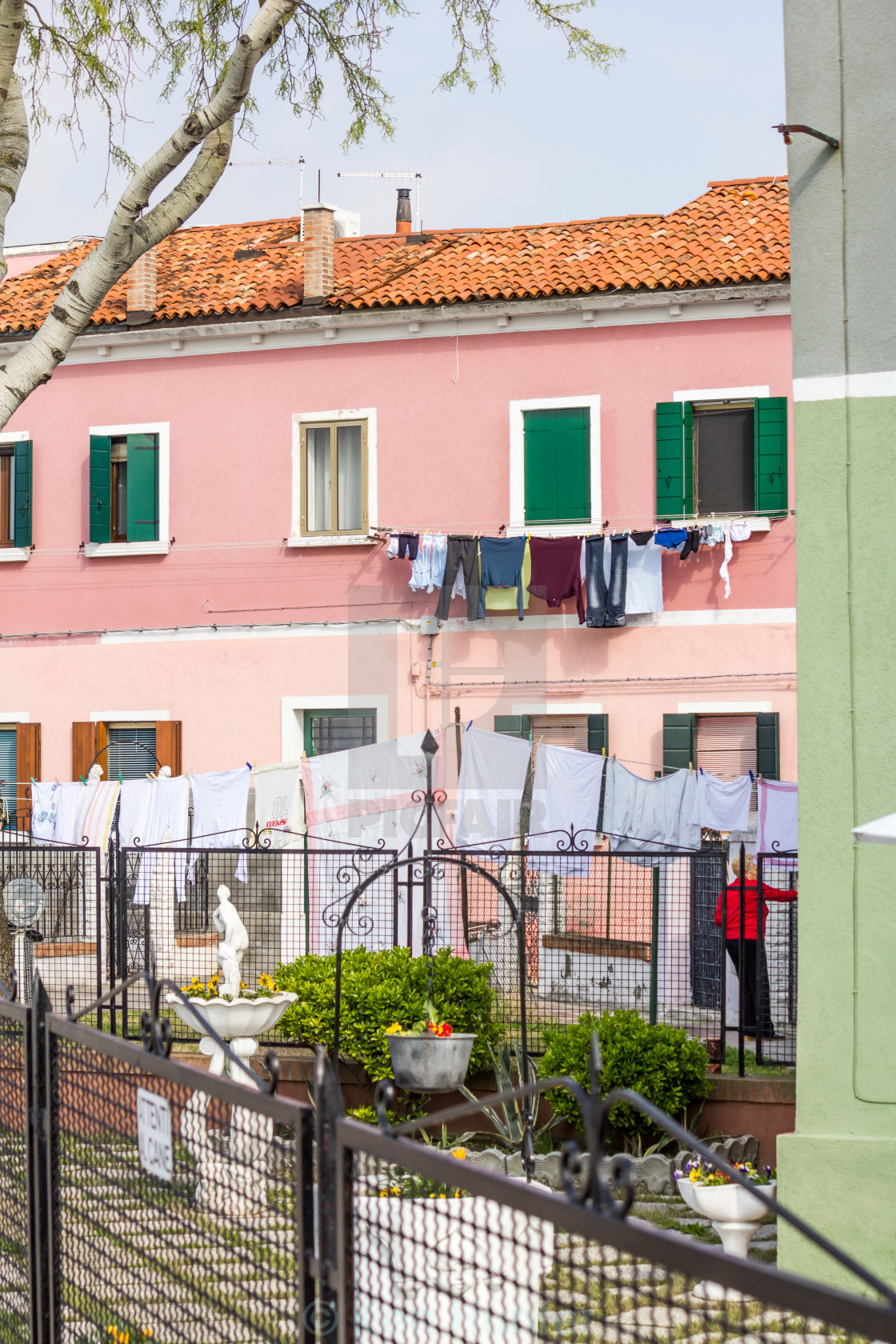 """Washing hanging out to dry amongst colorful houses in Burano, Venice"" stock image"