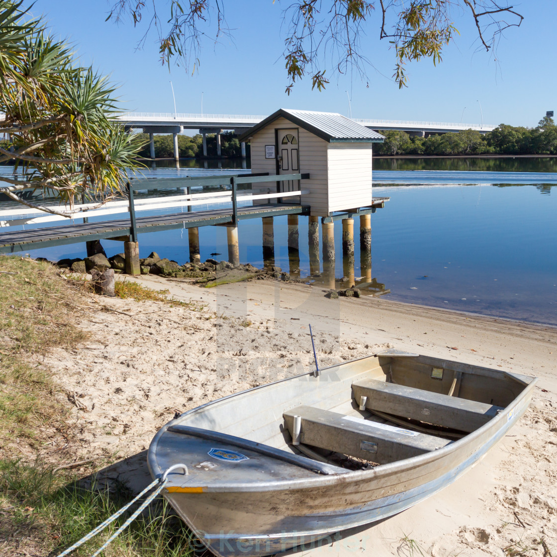 """Fishing cabin on Jetty with boat beached"" stock image"
