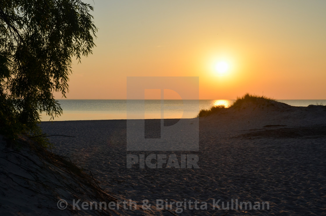 """Sunset by an empty sandy beach"" stock image"