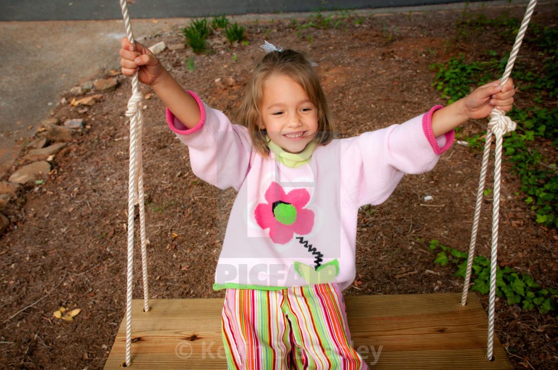 Little Girl Swinging in a Tree