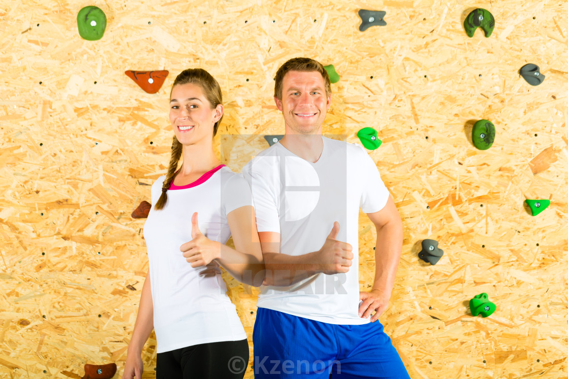 """Woman and man standing at climbing wall"" stock image"