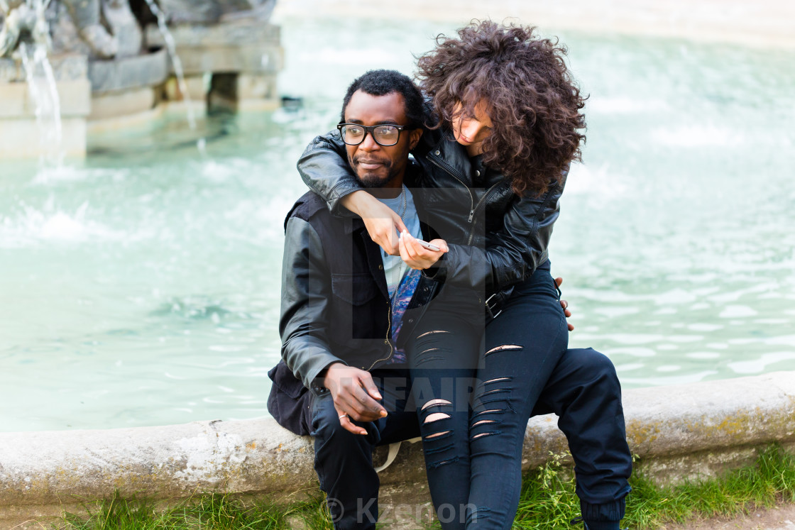 """African couple in city sitting at fountain"" stock image"