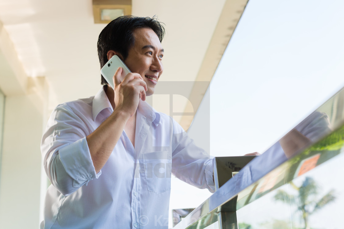 """""""Asian man telephoning on balcony with mobile phone"""" stock image"""