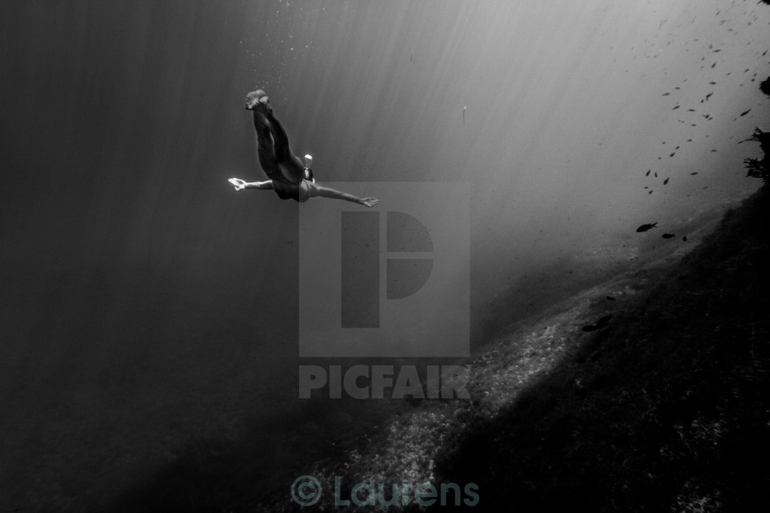 """Woman swimming into the abyss."" stock image"