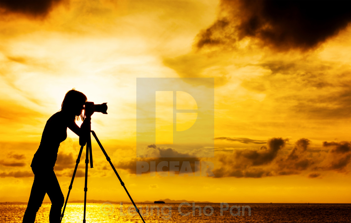 """""""Silhouette female photographer at sunset"""" stock image"""