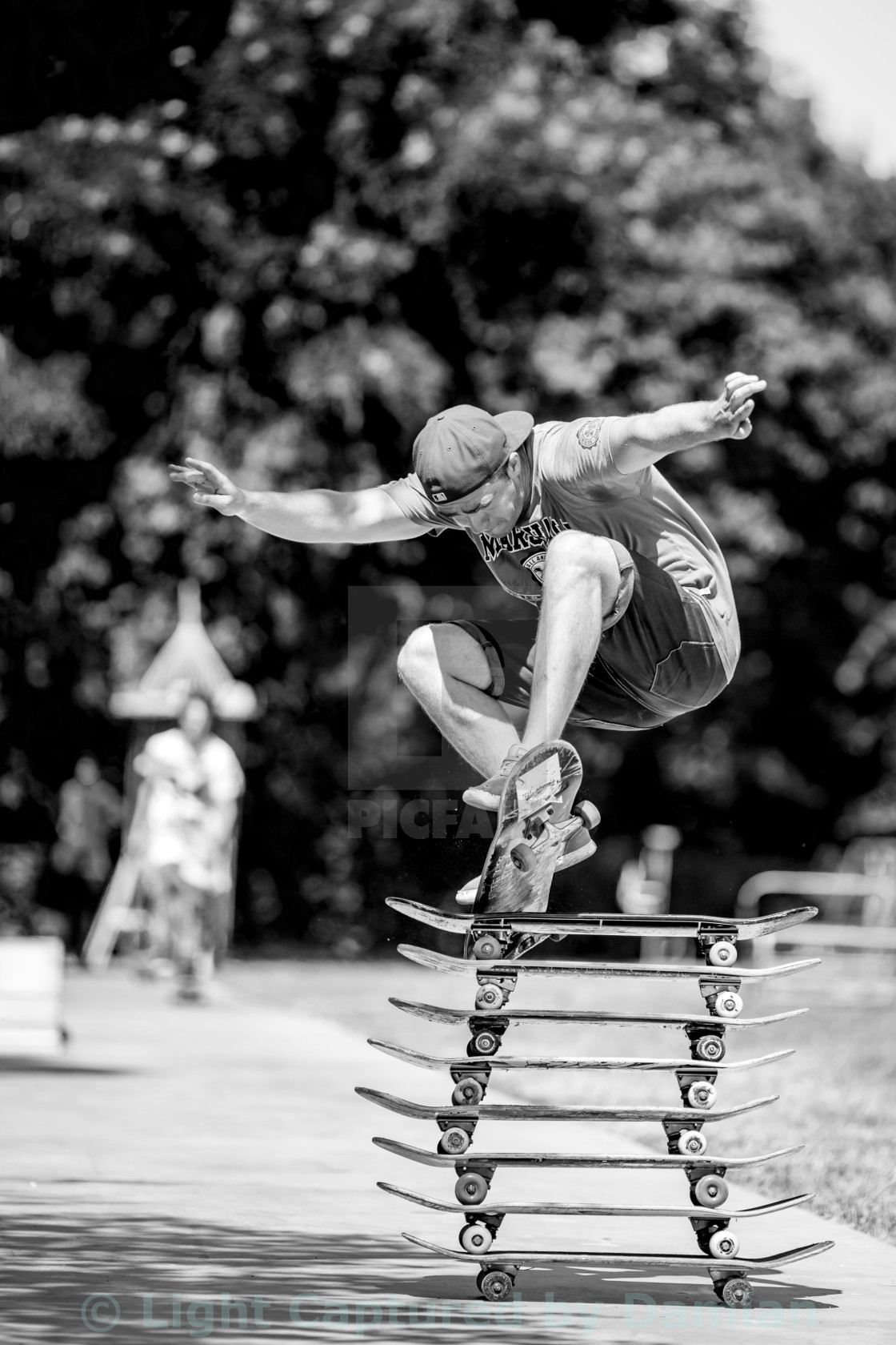 """Young man with hat jumping over stacked skate boards in a skateboard park during a sunny summer morning."" stock image"